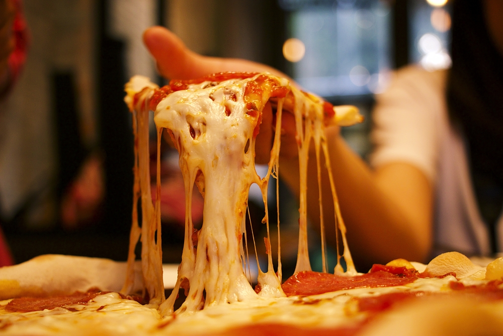 Very cheesy pizza slice in hand.Pizza is a savory dish of Italian origin, consisting of a usually round, flattened base of leavened wheat-based dough topped.