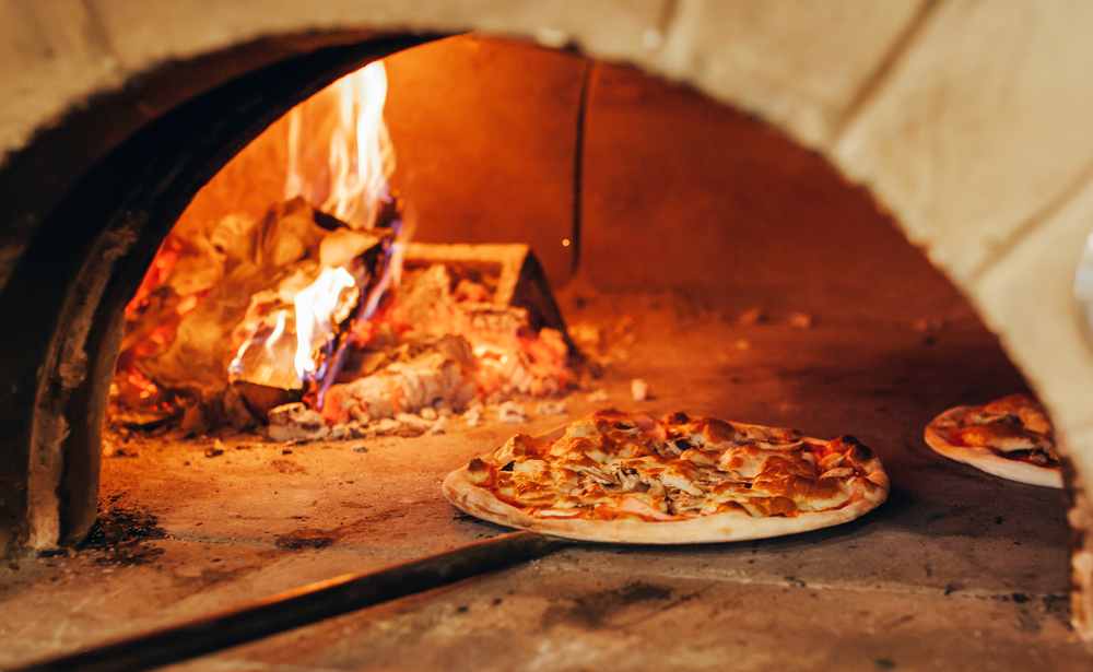 Italian pizza is cooked in a wood-fired oven. A
