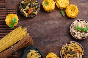 assortment of natural organic pasta on a wooden background