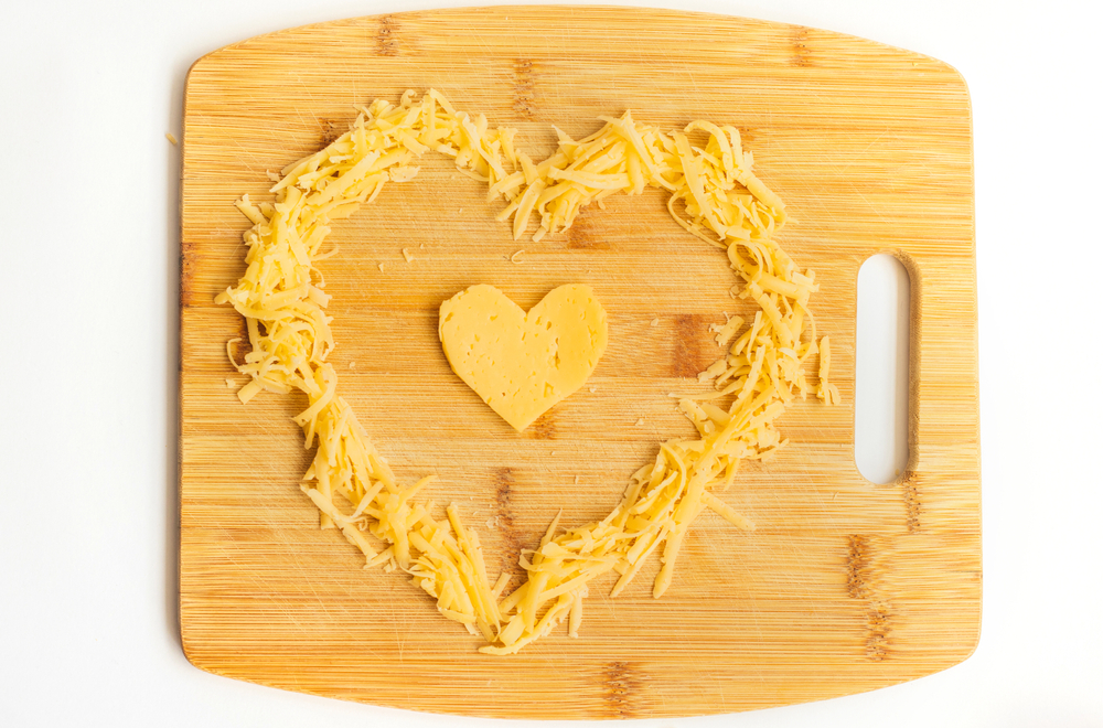 Cheese in the shape of a heart on a wooden Board. Grated cheese in the shape of a heart. Hard cheese.Cheese is for lovers.