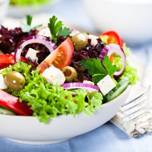 Greek salad with juicy tomatoes, feta cheese, lettuce, green olives, cucumber, red onion and fresh parsley. Homemade food. Symbolic image. Concept for a tasty and healthy vegetarian meal